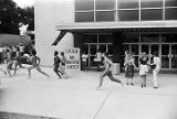 """Bodybuilders running in front of Boutwell Auditorium in Birmingham, Alabama, during the filming of the movie """"Stay Hungry."""""""