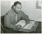 African American First Lieutenant Seth Finley seated at a desk and holding a ruler over a stack of papers, Fort Lewis, Washington