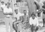 Men seated and standing in front of a tree in the dirt yard of a house in Newtown, a neighborhood in Montgomery, Alabama.