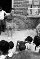 Woman speaking to children seated on the steps outside a brick building, possibly during a summer program.