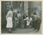Harlem residents in front of shop listening to the radio, 1930s