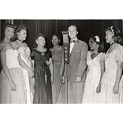 Man at WWSW radio station microphone flanked by seven young women in evening dress