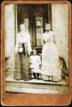 Two women and a child standing on step in front of a doorway of a house