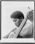 [Odetta, head-and-shoulders portrait, holding guitar]