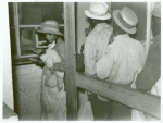 Negro day laborers brought in by truck from nearby towns, waiting to be paid off for cotton picking and buy supplies inside the plantation store, Friday night, Marcella Plantation, Mileston, Mississippi Delta, November 1939
