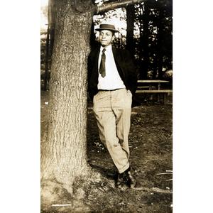 Postcard, man leaning against tree