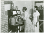 Ada Turner and Evelyn M. Driver Home Management and Home Economics Supervisor, canning English peas with pressure cooker in Mrs. Missouri Thomas' kitchen, Flint River Farms, Georgia, May 1939