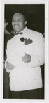 View of comedian Eddie Green, in a white jacket, speaking at an unidentified event, possibly a radio broadcast, circa 1940s