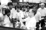 Man explaining scientific equipment to a group of students from Lee County, Alabama, during a field trip to Auburn University.