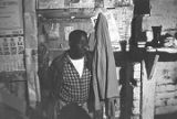 Roosevelt Bracy standing in the two-room shack where his family was living in Redland, Alabama.