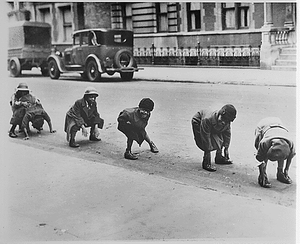 Black children playing leap frog in a Harlem street