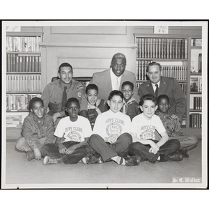 """""""Auspices of Boys' Clubs of Boston and Boston Council Boy Scouts,"""" including Jackie Robinson, the first African-American Major League Baseball player, center in the back row, posing together on Jackie Robinson Day at the Boys' Clubs of Boston Roxbury Clubhouse"""