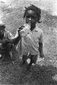 Little girl drinking from a glass soda bottle.