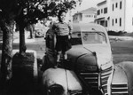Young boy standing on an automobile