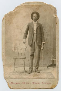 Portrait of an African-American Boy Standing Next to a Chair