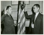 An African American man, Edward Swain Hope of Washington, D. C., is sworn in as a Lieutenant, CEC-V(S), USNR at Washington, D.C. by Lieutenant Commander H.B. Atkinson, USNR, Executive Officer of the Office of Naval Officer Procurement of Washington