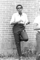 Stokely Carmichael standing against the wall of a brick church building in Prattville, Alabama, during a meeting of the Autauga County Improvement Association.