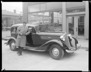 Jack Johnson posing next to a car in front of the Archer-Mann Motor Company, 4057 Lindell.
