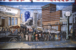 The exterior of this check cashing business is covered with a whimsical mural depicting an Afrocentric vision of Detroit in its 1920s heyday: the blue ghost of former Mayor Coleman Young (served 1974-1994) contemplates a thriving downtown from the skies and a tiny Henry Ford is shown driving one of his early automobiles. The largest building in the mural is Hudson's Department Store, which was second only to Macy's in New York City before being demolished in 1998. E. McNichols Road at Alcoy Avenue, Detroit, 2011