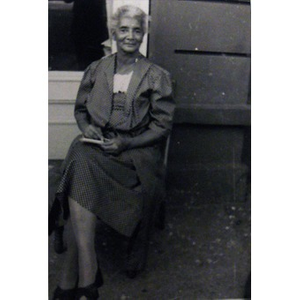 African-American woman sitting outside of a house