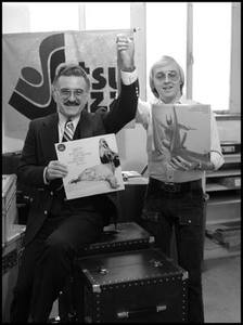 Student and Leon Breeden holding albums and clasping hands