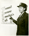 "African American Charity Adams, First Officer in the Women's Army Auxiliary Corps, standing in uniform and pointing to a poster that reads, ""Women! Answer America's Call, Serve in the W.A.A.C."""
