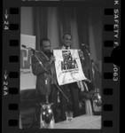 Music producer Quincy Jones and singer Harry Belafonte holding up autographed USA for Africa poster at press conference in Los Angeles, Calif., 1985