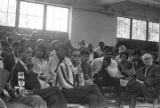 Audience listening to a young man speak while seated at the side of an auditorium or gymnasium.