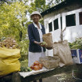 Hattie Dillard setting out vegetables at her produce stand, probably in Birmingham, Alabama.
