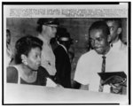[Ernest Green, the first African American graduate of Little Rock Central High School, and his parents are escorted to a taxi following graduation ceremonies]