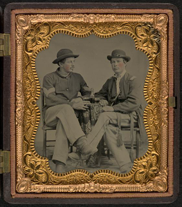 [Two unidentified soldiers in Union uniforms seated at a table and drinking]