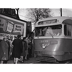 Men and women boarding the 85 Bedford trolley at intersection of Centre and Herron Avenues, with a Heinz billboard in the background
