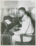 African American Private James C. Lee sitting at a teletype machine in the telegraph room at Camp Edwards, Kentucky