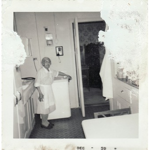 An elderly housekeeper poses in the kitchen.