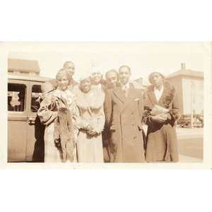 A group of people pose next to a car.