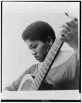 [Folksinger Odetta, head-and-shoulders portrait, facing left, holding guitar]