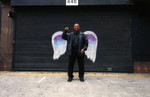 Unidentified man in a black leather jacket posing in front of a mural depicting angel wings