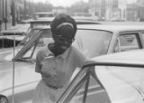 Woman standing next to a car parked on a street in downtown Montgomery, Alabama.