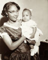 Mother poses with her infant daughter for a family portrait