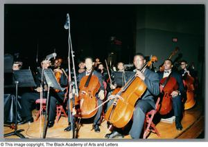 [Left-angled full shot of rows of some performers, with the majority in view are cellists] Christmas/Kwanzaa Concert