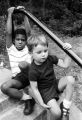 Two little boys seated on the steps outside a brick building, possibly during a summer program.