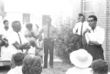 Stokely Carmichael speaking to a group of people standing outside a brick church building in Prattville, Alabama, during a meeting of the Autauga County Improvement Association.