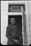 Jesse Fuller standing on front porch of his house at 1679 11th St, Oakland, California