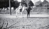 White girl on mule, African-American boy standing beside