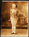 Young woman, probably a dancer, dressed in highly decorated tunic costume