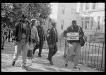 [African American men walking on a sidewalk, probably on Capitol Hill, during the Million Man March in Washington, D.C.]