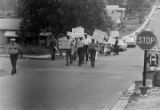 Small group of marchers carrying NAACP signs and marching through a neighborhood.