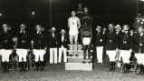 Sprinters Ralph Metcalfe and Paul Phillips with other athletes on victory stand, 1934?