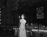 """Young woman performing on stage during a recording of the """"Sgt. Gene Autry"""" radio program at the municipal auditorium in Birmingham, Alabama."""