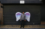 Unidentified man in a black cap posing in front of a mural depicting angel wings